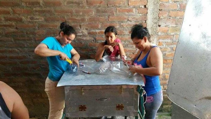 women recycling bottles on top of solar oven